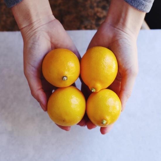 person holding 4 lemons