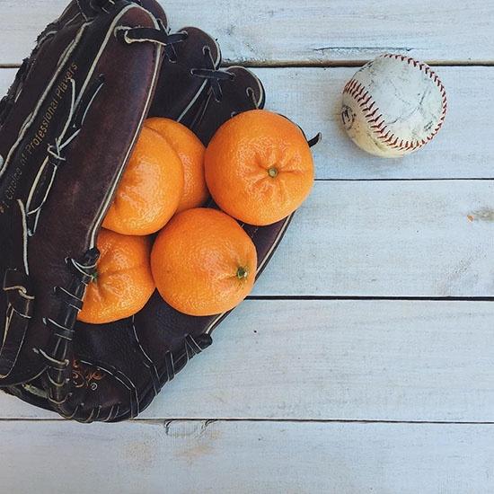 Dandy Clementines sitting in a baseball mitt